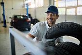 Happy repairman stacking car tires in auto repair shop.