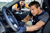 Auto repairman examining steering wheel on a car in a workshop.