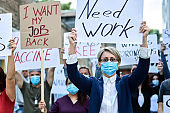 Businesswoman with protective face mask on a protest during coronavirus pandemic.