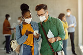 Happy university friends using smart phone while wearing face masks in a hallway.