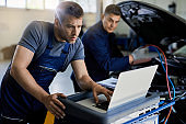 Mid adult mechanic using laptop while running car diagnostic in auto repair shop.