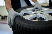 Close-up of a mechanic working with car tire in auto repair shop.