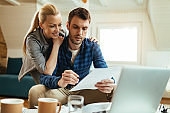 Happy couple communicating while going through home finances.