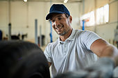 Happy mechanic working with tires at car service workshop.
