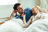 Happy couple having fun while talking in bedroom in the morning.