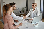 Happy real estate agent shaking hands with a couple on a meeting in the office.