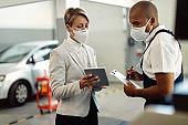 Businesswoman and African American mechanic wearing face masks and cooperating while using touchpad in a workshop.