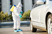Sanitation worker in protective suit spraying car tire during city disinfection due to COVID-19 pandemic.