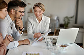 Young couple and real estate agent analyzing housing plans with a couple in the office.