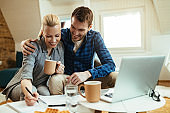 Happy couple writing notes while going through home finances during their coffee time.