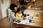Black single mother taking notes and working while babysitting her kids at home.