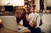 Happy father and daughter waving during video call at home.