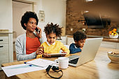Working black mother with two children talking on cell phone at home.