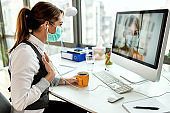 Businesswoman with face mask having video chat with her colleague in the office.