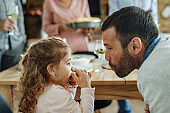 Father and daughter sharing a spaghetti while having lunch in dining room.