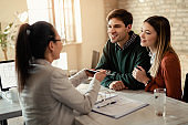 Young couple having a meeting with real estate agent in the office.