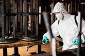 Disinfection worker in hazmat suit spraying contaminated cafe due to coronavirus epidemic.