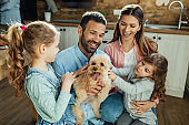 Happy parents and their daughters having fun with a dog at home.