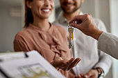 Close-up of couple receiving new house keys from real estate agent.