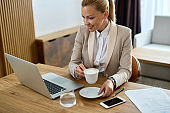 Happy businesswoman drinking coffee while using laptop in hotel room.