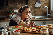 Young happy woman preparing food and making bruschetta in the kitchen.
