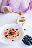 Woman sitting at the table and pouring honey on cereals with milk and fruits breakfast meal.