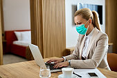 Businesswoman wearing face mask while working on laptop in hotel room.