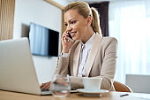 Happy businesswoman talking on the phone while using laptop in hotel room.