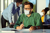 College student with face mask thinking while having an exam in the classroom.