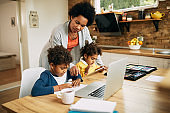 African American mother assisting her kids in learning at home.