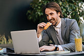 Happy entrepreneur working on laptop while eating croissant in a cafe.