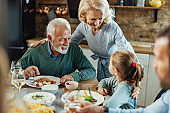 Happy grandparents talking with their granddaughter at dining table.
