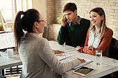 Young couple having a meeting with insurance agent in the office.