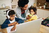 Black single mother giving her kids an apple for a snack during homeschooling.