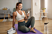 Happy sportswoman using cell phone while relaxing on the floor at home.