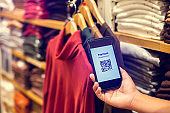 Selective focus to payment QR code tag on smartphone with blurry many clothes in the store to accepted generate digital pay without money.