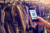Selective focus to payment QR code tag on smartphone with blurry many cloth shoes in the store to accepted generate digital pay without money.