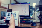 Selective focus to customer hand holding smart phone to scan Qr code payment and barcode with blurry online shopping website on computer screen.