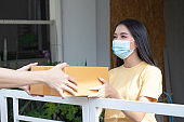 Delivery man holding a cardboard box in front of house and Asian woman wearing face mask accepting a delivery of box from deliveryman during COVID-19
