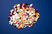 Close-up multi-colored pills and tablets on blue background