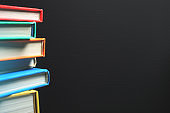 Close-up on Stack of Books Against Blank Blackboard Background