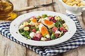 Delicious Italian salad with salami, egg, crostini and mozzarella.