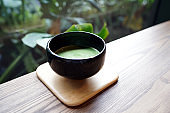 Hot Matcha - A bowl of green tea latte on wooden table and copy space, Traditional Japanese drink.