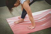 Young Asian woman is exercising on a movement mat outdoor.