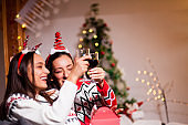 Happy female friends enjoying new year party at home
