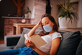 Woman with protective face mask reading a book at home.