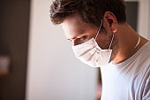 Portrait of man wearing surgical mask at home. Covid-19, coronavirus and quarantine concept.