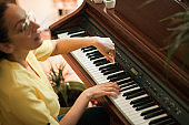 Young Woman Playing Piano in Domestic Room