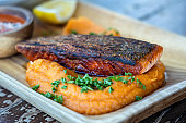 Fried salmon fillets served with vegetable garnish on wooden plate and sauce. Roasted salmon filet with sweet mashed potatoes.