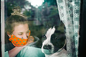 Woman wearing medical mask, standing near the window with dog